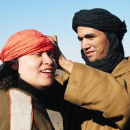 A local Berber guide helps a group member with her head scarf, Sahara Desert, Morocco.