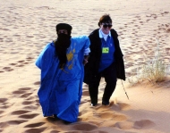 A Blueman helps a Ya'lla traveler climb a dune in the Sahara Desert of Morocco. Tuareg Berbers are known as Bluemen because of their traditional blue scarves and robes.