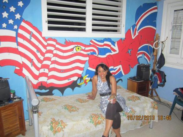 Tania at her house in Havana, with a mural painted by her son.